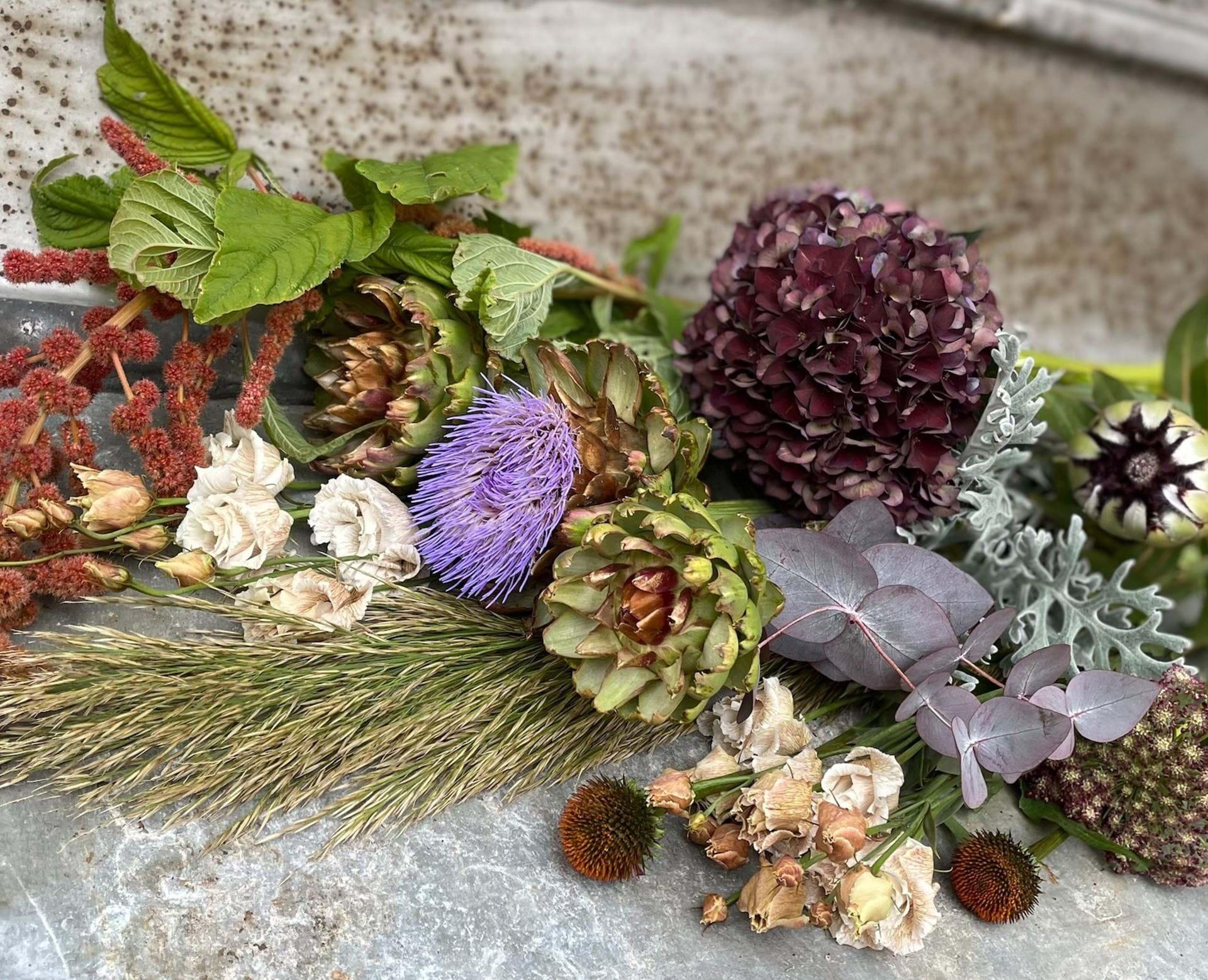 Forskellige blomster og dekorationsmaterialer i efterårsfarver